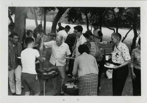 Man serving up hamburgers to students at the geography department picnic