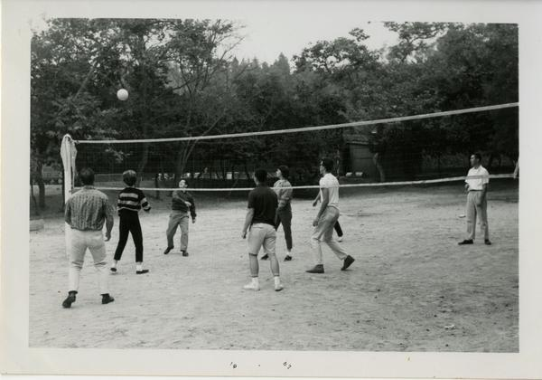 People, presumably of the geographic department, playing volleyball, possibly at the geography department picnic