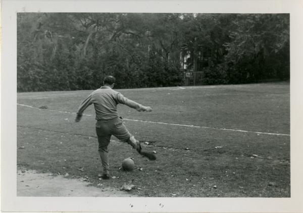 Man, possibly from the geography department, kicking a soccer ball
