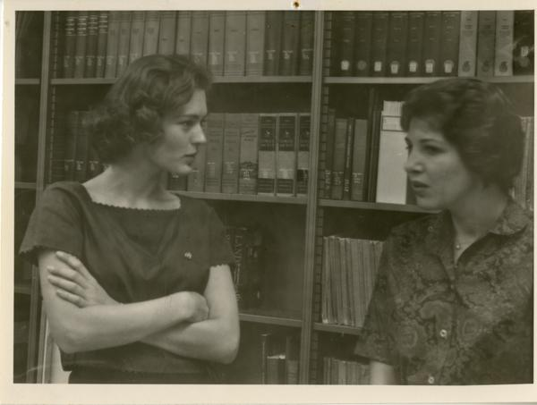 Women, presumably of the geography department, talking in the library