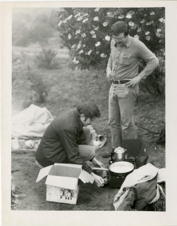 Men of the geography department preparing food on a portable stove