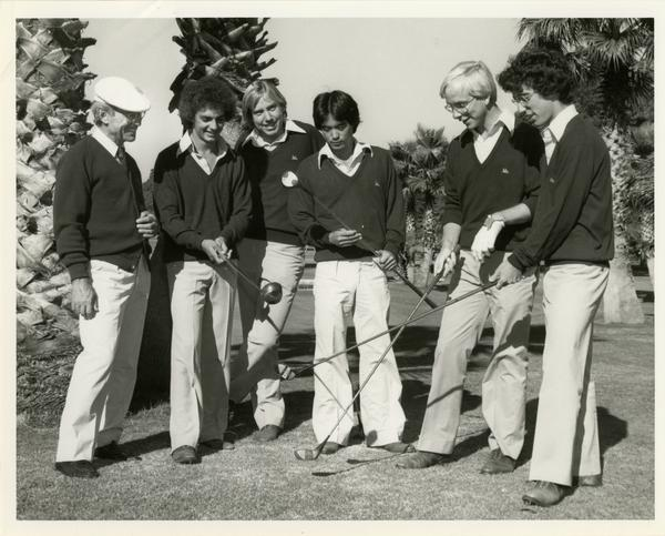 Members of the Golf Team with golf clubs on the field, ca. 1980's