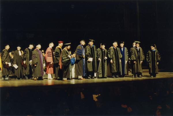 The Emeriti from 1937-1938 Faculty and ceremonial escorts standing on stage during PhD Hooding Ceremony, June 1989