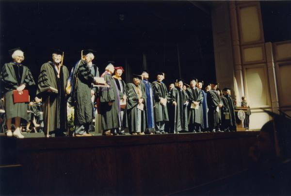 The Emeriti from 1937-1938 Faculty and ceremonial escorts standing on stage during PhD Hooding Ceremony, June 1990