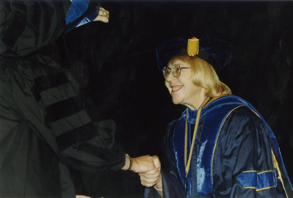Victoria Fromkin shaking hands with graduate, June 1989