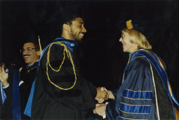 Robin Kelley shakes hands with Victoria Fromkin with Edward Alpers stands in the background during Hooding ceremony, June 1988