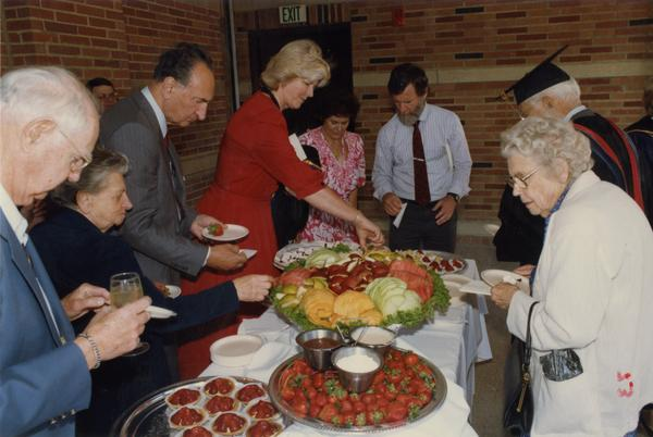 Thomas Jacobs and Mrs Francis Black stand with others around buffee table, June 1988