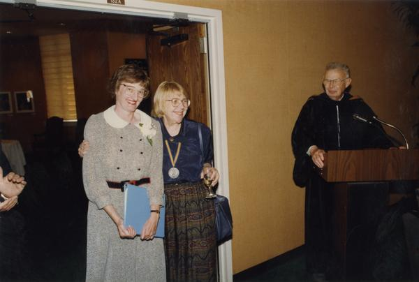 Victoria Fromkin hugs Beverly Liss with Raymond Fisher looking on from podium, June 1988