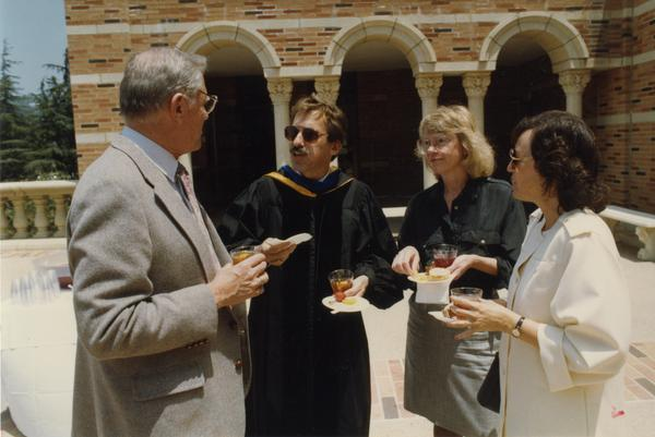 Chancellor Young, Edward Alpers, Carol Hartsog and Bea Mandel gather together outside of Royce Hall after PhD Hooding Ceremony, June 1988