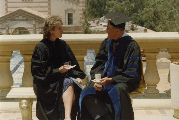 Couple sits on bench beside Royce Hall with Kaufman Hall in the background, June 1988