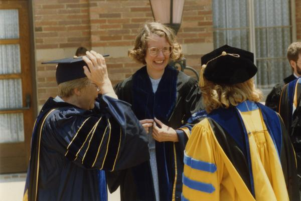 Three Faculty members stand outside Royce Hall during gathering for PhD Hooding Ceremony, June 1988