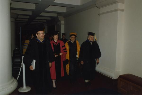 Malcolm, Wally Goldschmidt and others walk down hall during PhD Hooding Ceremony, June 1988