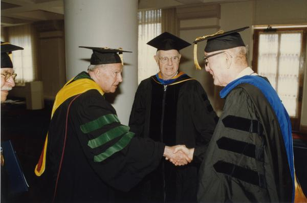 Franklin Murphy and Thomas Jacobs with unidentified man prepare to line up for PhD Hooding Ceremony, June 1988