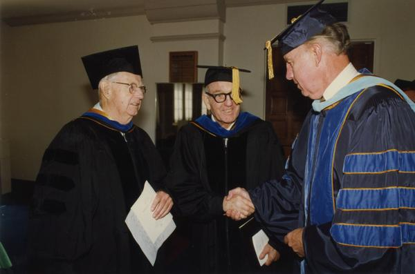 Thomas Jacobs, Elwin Svenson and unidentified man chat before lining up for PhD Hooding Ceremony, June 1988