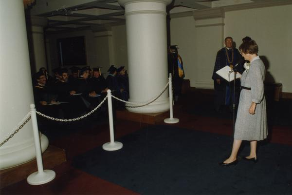 Beverly Liss reads out instructions for faculty march before PhD Hooding Ceremony, June 1988