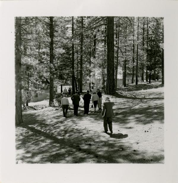 Group walks through trees at Lake Arrowhead Lodge grounds, March 1959