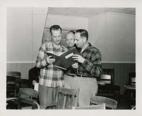 Three men gathered around a book at the Lake Arrowhead Conference Center