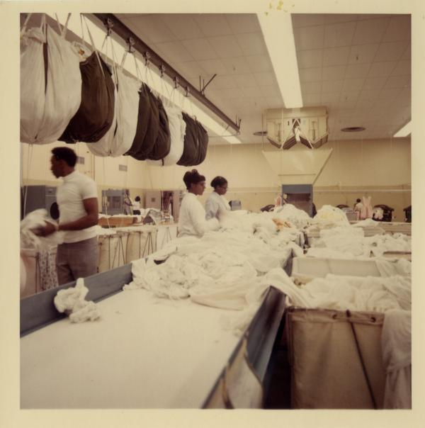 Three laundry workers sort at UCLA Laundry Facility