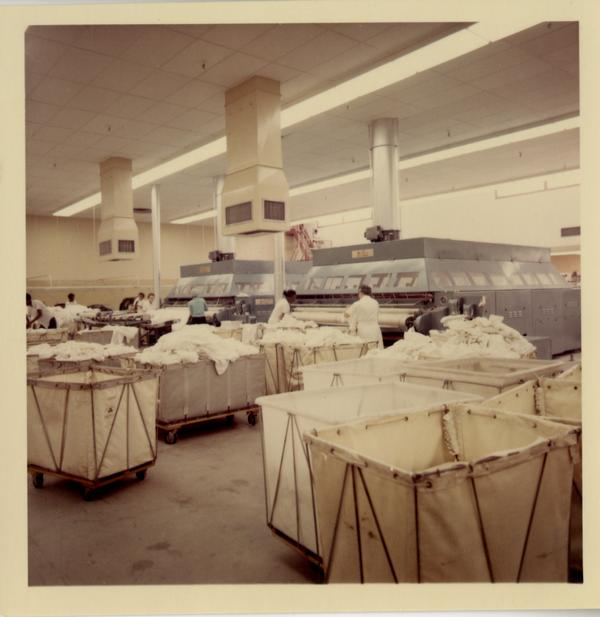 View of laundry workers at stations in UCLA Laundry Facility