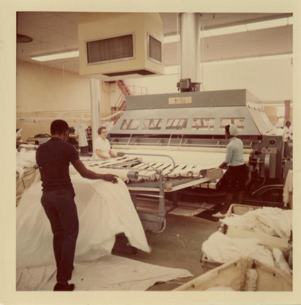 Laundry workers using machinery at UCLA Laundry Facility