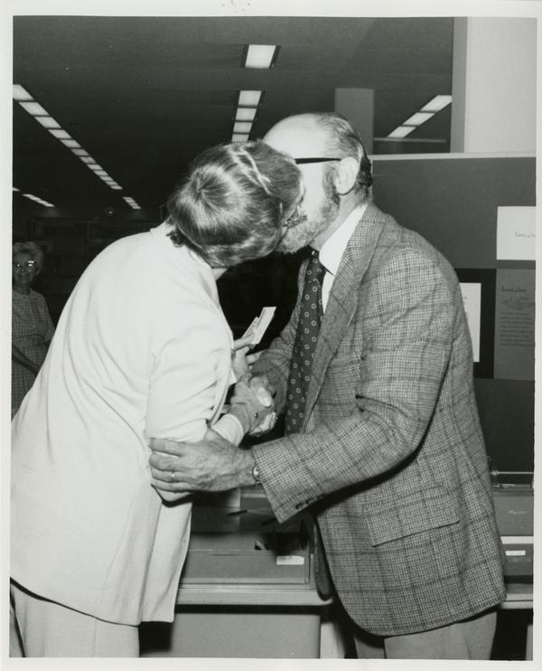 Page Ackerman and Jim Cox kissing as they shake hands
