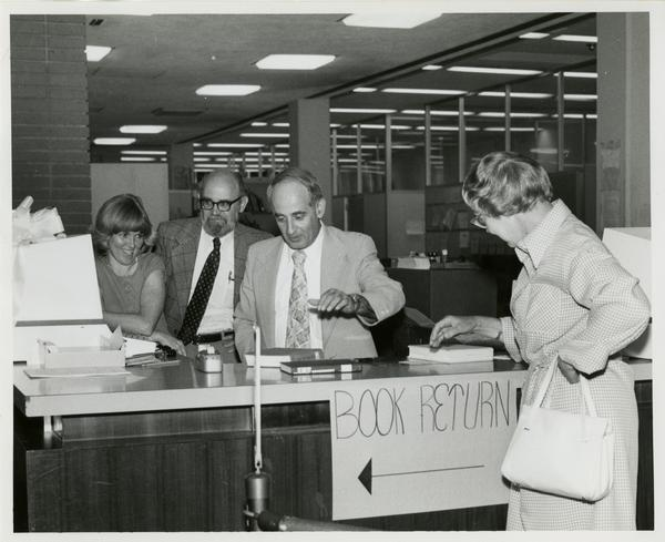 Linda Fierro, Jim Cox, and Russell Shank stand behind desk as Page Ackerman walks up