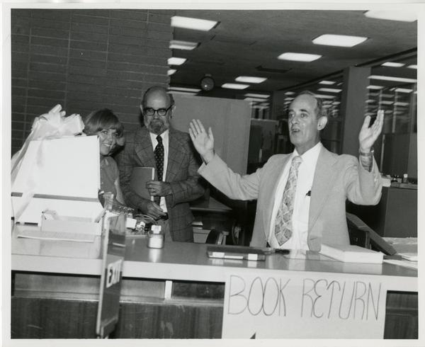 Linda Fierro, Jim Cox, and Russell Shank stand behind desk with new computer