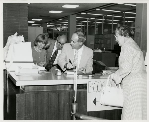 Linda Fierro, Jim Cox, and Russell Shank look at computer as Ackerman stands on other side of the desk