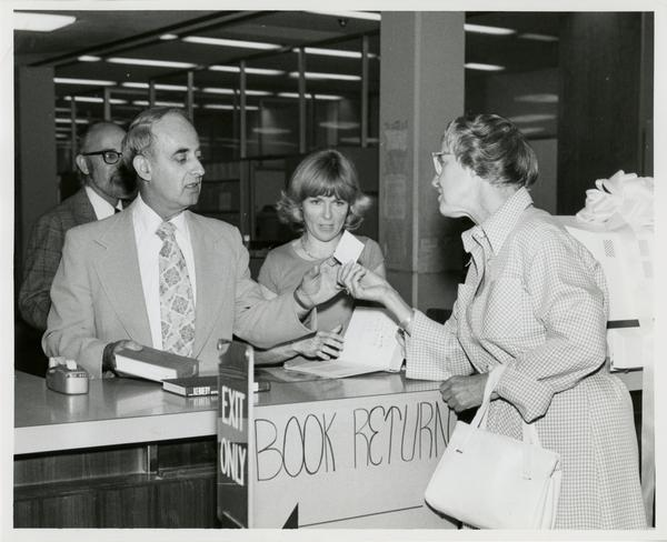 Page Ackerman hands card to Russell Shank while Jim Cox and Linda Fierro stand in background