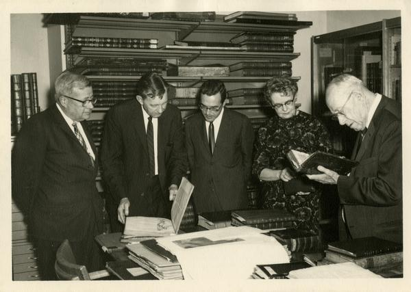 Chancellor F. D. Murphy Dr. Bennett Allen, and Mrs. Boris Krichesky viewing the gift collection of medical history books given to the Biomedical Library