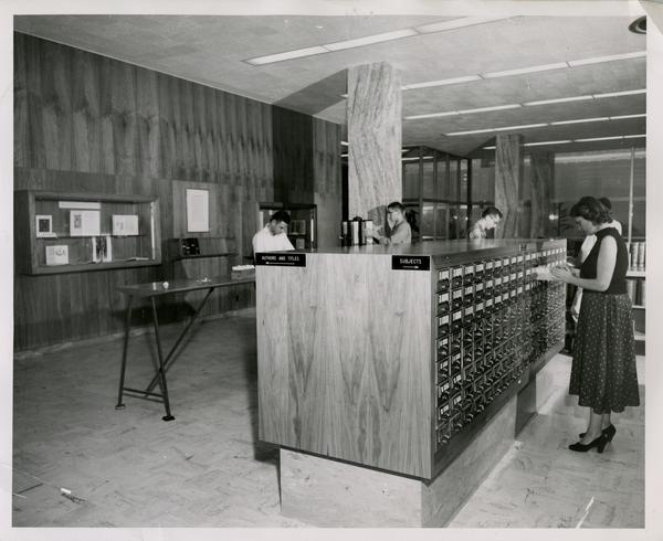 Students searching in Biomedical Library card catalog