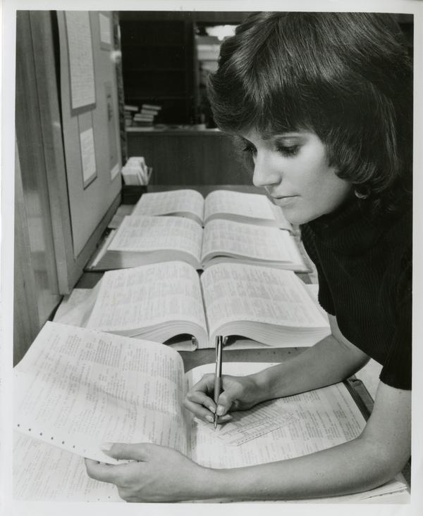 A clerk in the UCLA Biomedical Library checks on a periodical in one of the reference volumes