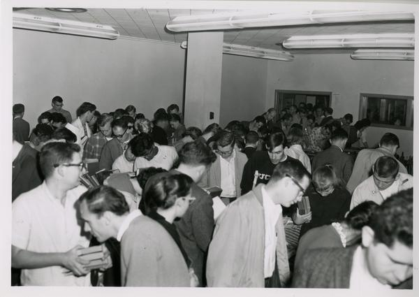 Crowd searching through books at 1962 sale of library duplicates