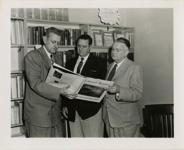 Three men looking photography book by Edward Weston, ca. 1953