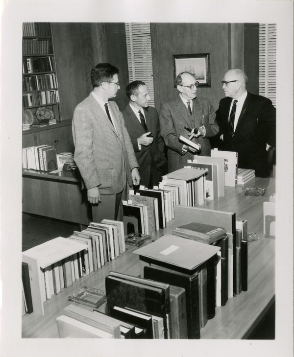 Group of men looking at books, ca. 1953