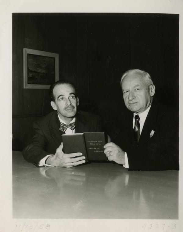 Dwight L. Clarke and Lawrence Clark Powell holding one millionth volume, November 10, 1953