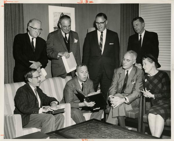 The UCLA Library's two millionth book is examined by Chancellor Franklin D. Murphy at the 1964 presentation ceremony as Robert Vosper, Regent Edward W. Carter, Mrs. Elmer Belt, Dr. Elmer Belt, Prof. Majl Ewing, W. Thomas Davis, Prof. C.D.O'Malley sit and stand beside him.