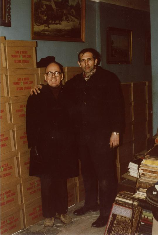 Two men standing beside boxes in Music Library at Schoenberg Hall