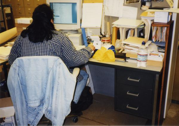 Library Special Collections staff member working at desk, ca. 1997