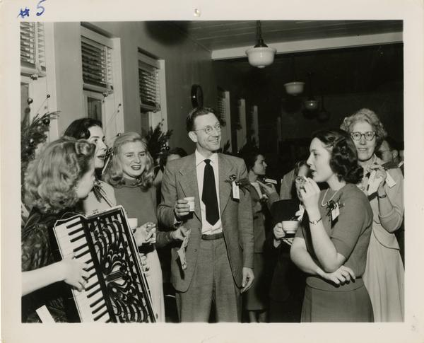 Neil Harlow stands in middle of group of library staff while woman plays accordian at Library Christmas party
