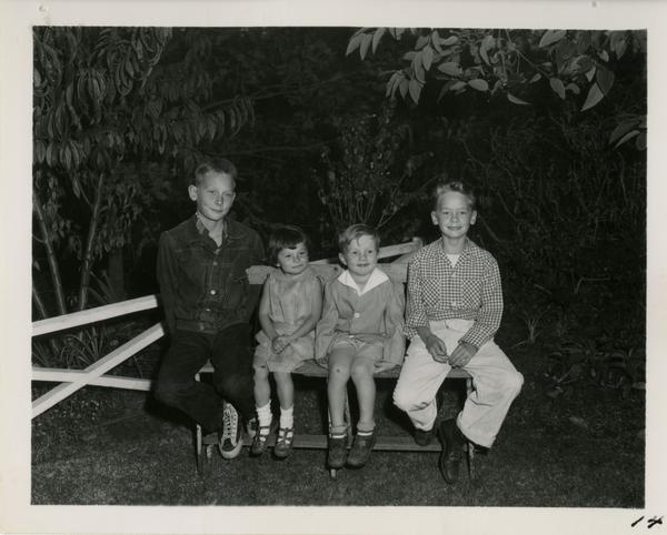 Children of guests sit on bench at party