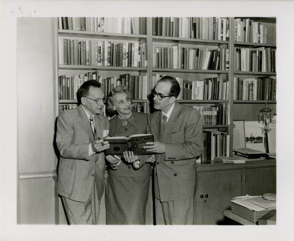 Lawrence Clark Powell holding book with colleagues