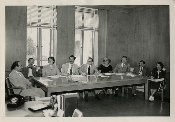 Lawrence Clark Powell sitting at end of table speaking to colleagues