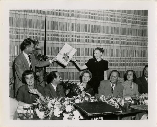 Page Ackerman, Lawrence Clark Powell, Mrs. Elmer Belt, and Chancellor Allen sitting as two other staff exhange gift at Library staff Christmas party, December 19, 1957