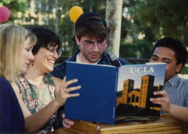 Library staff members looking through UCLA anthology at retirees party, ca. 1991