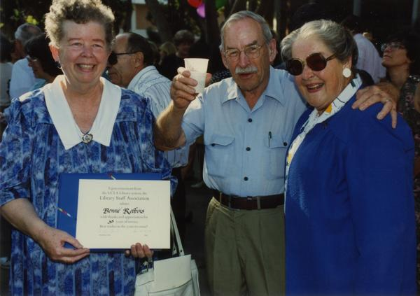 Library staff holds up her certificate while other staff members cheer and smile for the camera, ca. 1991