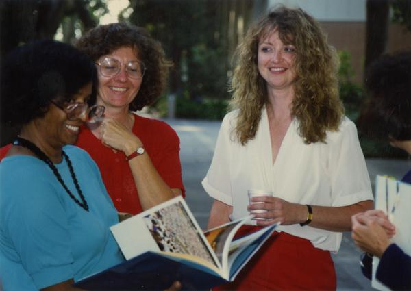Library staff looking through a book, ca. 1991