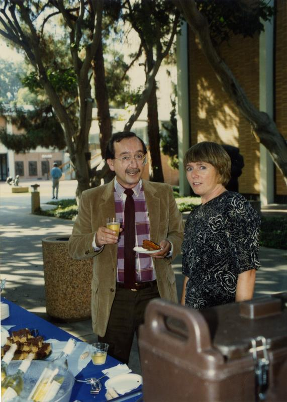 Library staff standing in front of the food table, mid-conversation, ca. 1991