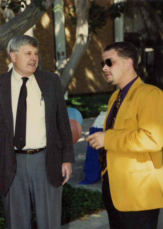 Two staff members talk with each other at a staff event, ca. 1991