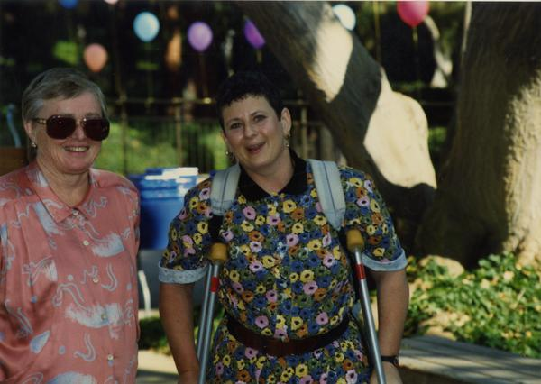 Two library staff members smile for the camera at a staff event, ca. 1991